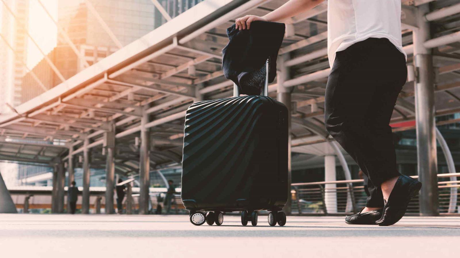 """אישה עם מזוודה בדרך לעבודה בחו""""ל"""